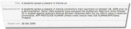 Bildunterschrift: A students sprays a placard in Vienna university