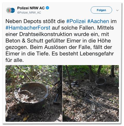 Screenshot eines Tweets der Polizei Aachen - Neben Depots stößt die Polizei Aachen im Hambacher Forst auf solche Fallen. Mittels einer Drahtseilkonstruktion wurde ein mit Beton und Schutt gefüllter Eimer in die Höhe gezogen. Beim Auslösen der Falle, fällt der Eimer in die Tiefe. Es besteht Lebensgefahr für alle. - Dazu ein Foto eines mit Erde verschmutzten Eimers, der mit Beton gefüllt ist. Aus dem Beton guckt ein Drahtseil raus