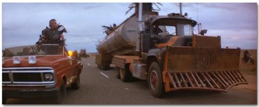 [Zu sehen ist der gleiche Tankwagen, diesmal aber in einem anderen Bildausschnitt. Neben dem Wagen fährt noch ein anderes Auto mit einem kostümierten Menschen drin. Es ist ziemlich deutlich zu erkennen, dass es sich um eine Filmszene handelt.]