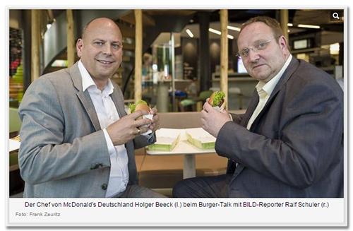 Der Chef von McDonald's Deutschland Holger Beeck (l.) beim Burger-Talk mit BILD-Reporter Ralf Schuler (r.) [Auf dem Foto sitzen die beiden nebeneinander, schauen in die Kamera und halten einen Burger in der Hand]