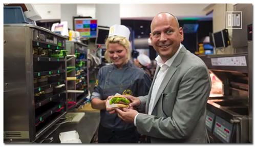[Der McDonald's-Chef nimmt von einer Mitarbeiterin einen Burger entgegen]