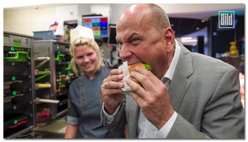 [Er beißt hinein, während die Mitarbeiterin im Hintergrund erwartungsvoll lächelt]