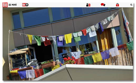 Screenshot Bild.de - Foto, das viele bunte Stoffstücke auf zwei Leinen auf einem Balkon zeigt